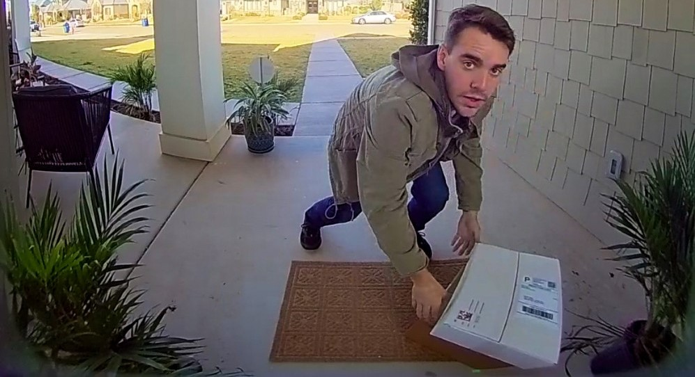 This is an image of a man stealing a package from a porch.